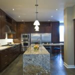 L Shaped Island Ice Brown Granite Countertop Pendant Lights Brown Cabinet Stainless Steel Appliances