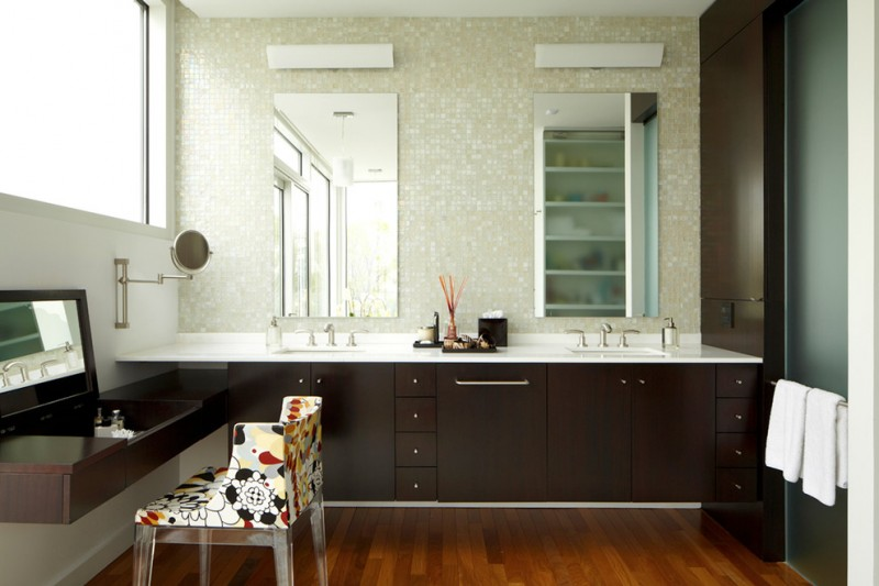 L shaped vanity with wooden cabinet, white countertop with two sinks, medicine cabinet mirror, makeup area with convertible mirror