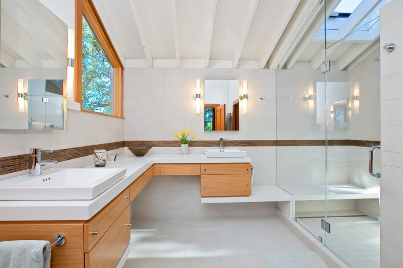 L shaped vanity with wooden cabinet with satin finish, white caesarstone top, two sinks on both ends, white porcelain floorin, white walls, sconces on mirror sides