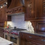 Victorian Kitchen With Dark Brown Island, Cabinet, Wall Mounted Cabinet, Chimney, And White Backsplash, Silver Oven And Stove,