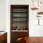 A Brown Wooden Built In Shelves With White Marble Bar Counter Top, Glass Shelves On Top And Wooden Cabinet Under