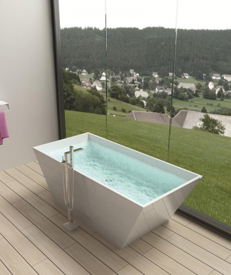 a lone white small standing bathtub near the window