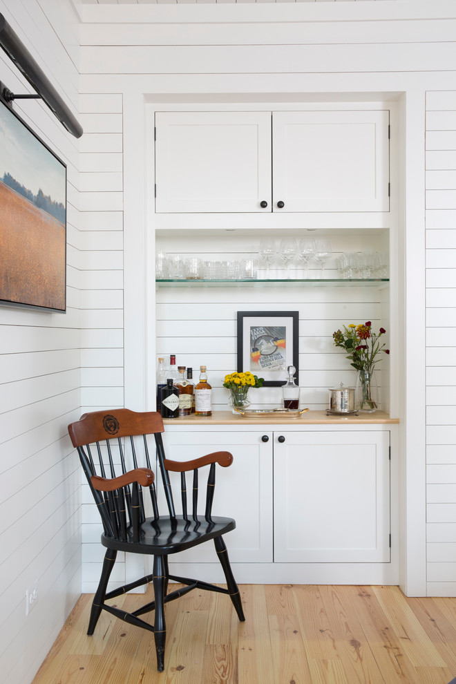 a nook in the white wooden wall with glass shelves and brown wooden counter
