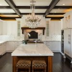arabesque backsplash kitchen window ceiling lights hardwood floor chandelier stools wall cabinets