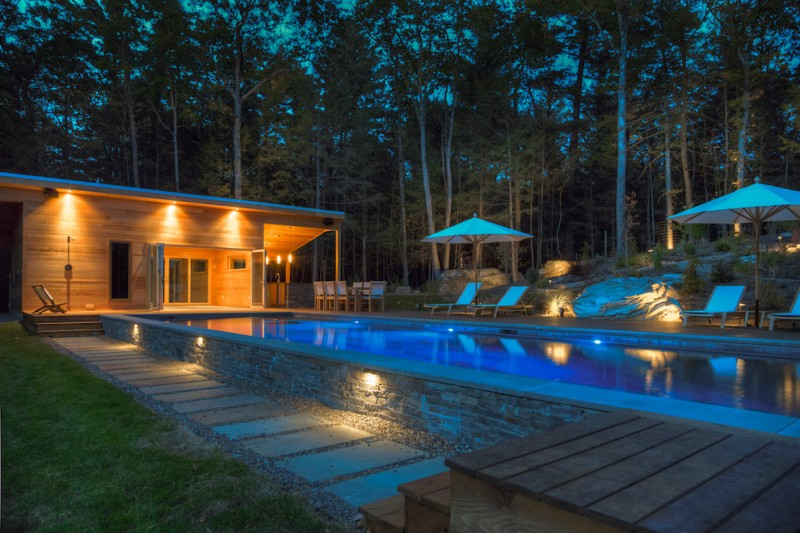 backyard with long rectangle pool, wooden deck, rectangle tiles path, pools umbrella, pool lounges