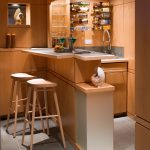 Bar In Basement Made From Wood, With Bottle Rack Against The Wall, Sink, Wood Board In The Counter Top, Bar Stools