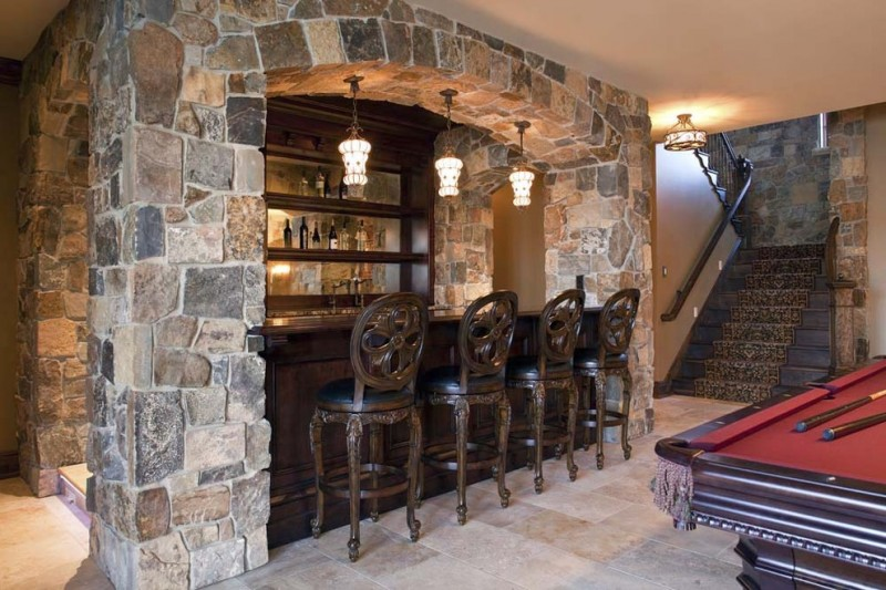 bar under the stones arch ceiling with withered wood table and cabinet, withered wood chair with back, three yellow classic pendant