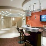 Bar With Orange Wal, Wall Mounted TV, Silver Pendant, Silver And Brown Counter Top, Black Orange Stool
