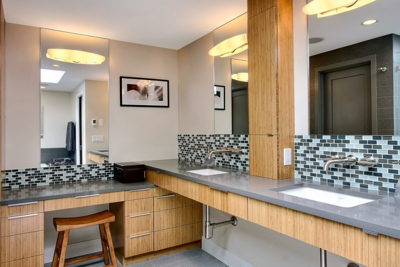 bathroom with brown wall, black and grey mozaic tiles bakcsplash, wooden cabinet under the vanity, doble sinks on one side, three mirrors