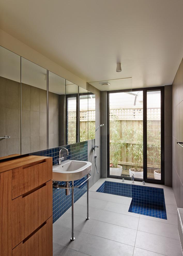 bathroom with grey tile flooring, blue mosaic tiles in built in bathtub and a shower on top , in backsplash sink