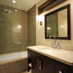 Bathroom With White Bathtub Covered In Mosaic Tiles, Silver Round Rain Shower On Top And Moveable Shower Under