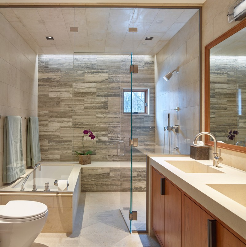 bathroom with white bathtub covered with brown tiles outside, near a shower area