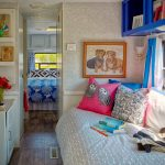 Bed In Trailer With White Comforter, Colorful Pillow, White Cabinet And Table