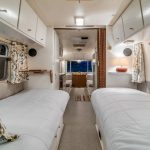 Bedroom In Trailer With White Cabinet On Top, Low Bed In White, Curtain