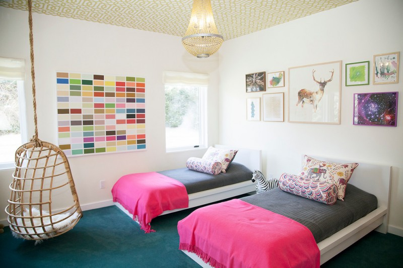 bedroom with white wall, brown ceiling, white wooden bed platform, green rug flooring, rattan swing, chandelier