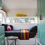 Bedrooom In Trailer With White Wooden Platform Frame And Table, Green Cabinet, Green Cupboard, Wooden Flooring, Rug