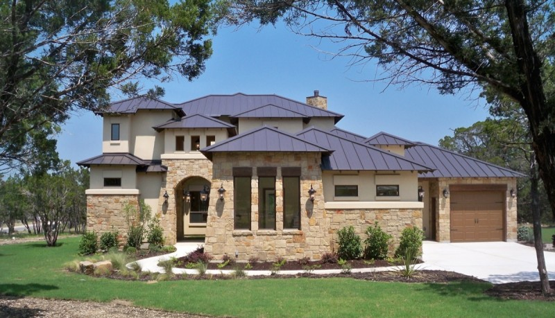 bijou texas hill country home plan with dark brown roof with wooded area