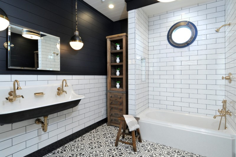 black and white tile subway tile black walls trough sink drop in tub wooden storage wooden chair brass tap