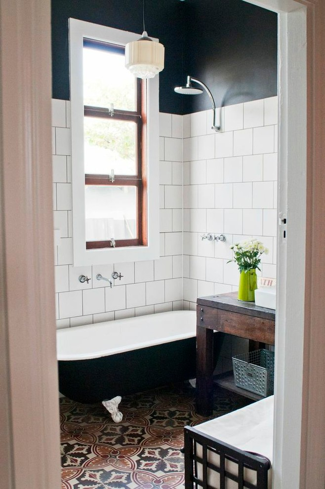 black clawfoot tub with white inside and rain shower on top