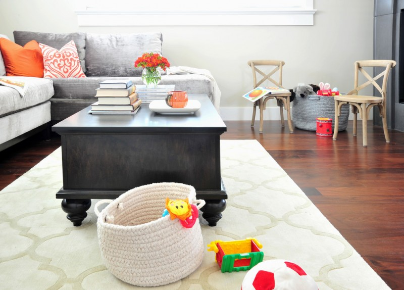 black paint rectangular coffe table colorful soft woven baskets brown walls medium tone hardwood floors a standard fireplace white rug wooden chair