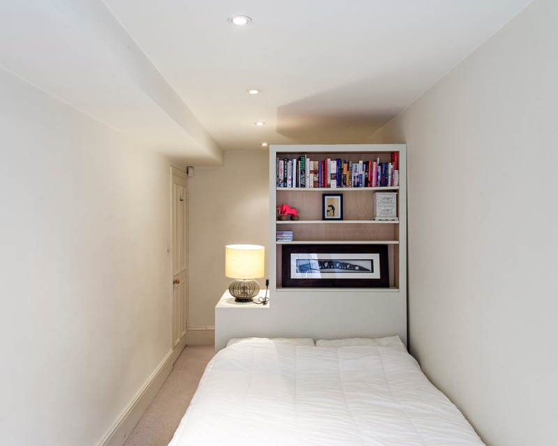 bookcase as headboard and bed side table for compact bedroom concept