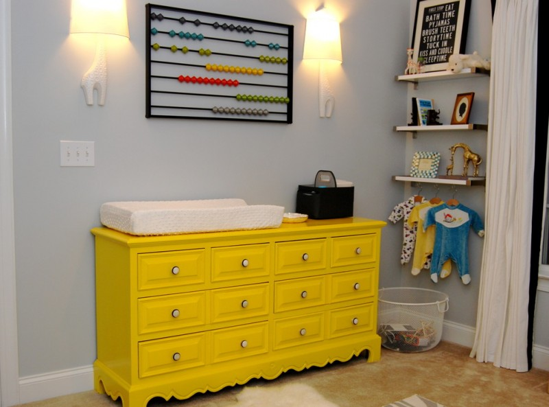 bright yellow nursery table with under storage light blue painting walls colorful wall ornaments wall mounted shelves for baby's properties