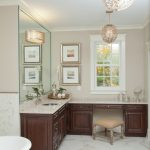 Brown Bathroom With L Shaped Vanity In Brown Top, Brown Wooden Cabinet, Brown Wall, Window On One Side, Large Mirror