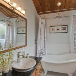 Classic Traditional White Tub With Rain Shower In The Middel Top Closed By White Curtain Around The Tub