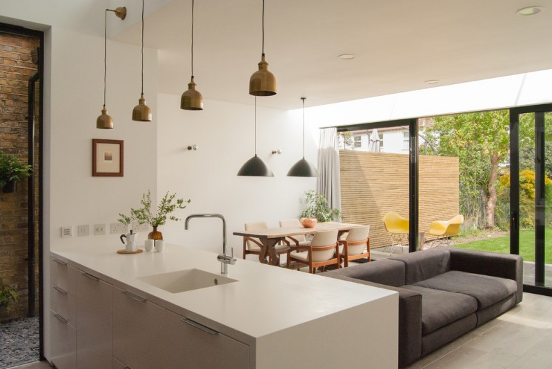 combination of dining, kitchen and living chairs table pendant lights sink faucet glass door contemporary room
