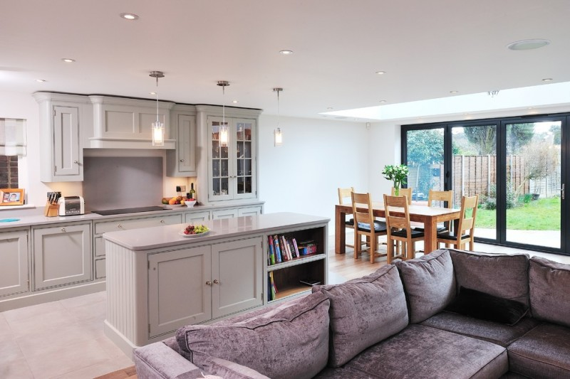 combination of dining, kitchen and living chairs table sofa bookshelves glass door hanging lights cabinets