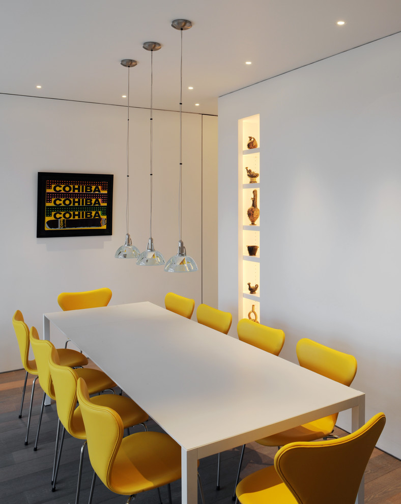 contemporary dining room with clean white dining table yellow dining chairs dark toned wood floors modern pendant lamps modern wall art