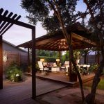 Contemporary Gazebo With Wooden Deck Flooring, Wooden Poles, Wooden Beam Ceiling, Chandelier, White Chairs And Tables Sets