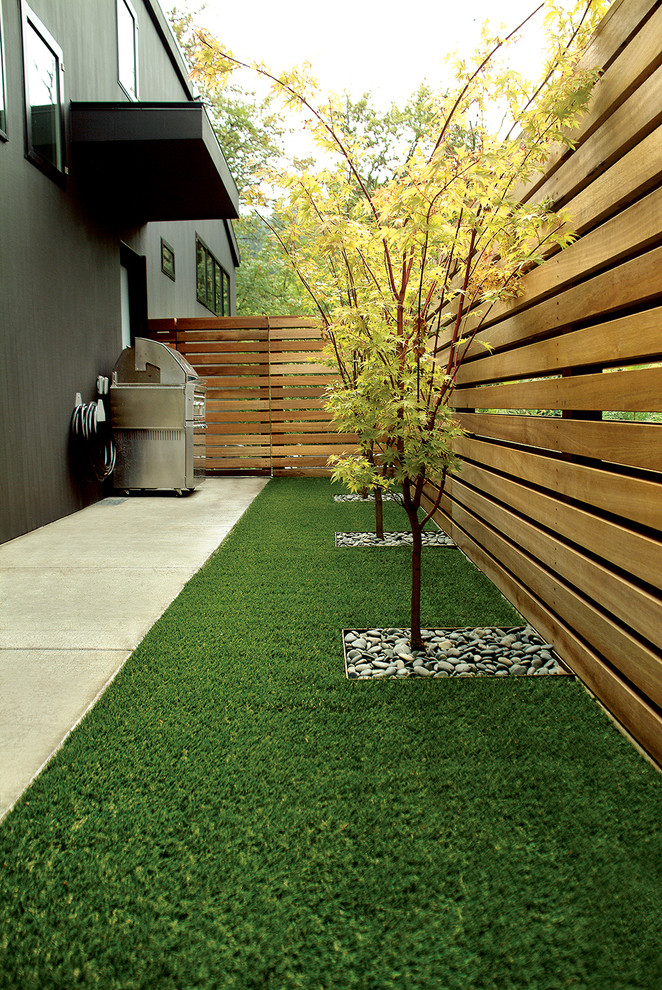 contemporary landscape with grass carpet, some plants put by itself, wooden rails