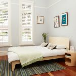 Contemporary Plywood Bed With Headboard Bedroom Rug With Multicolor Stripes Pattern Contemporary Plywood Bedside Tables Medium Toned Wood Floors Light Blue Walls Glass Windows With White Shutters