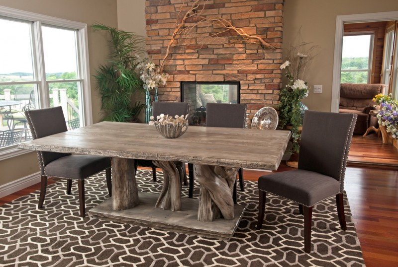 cool shabby dining wood table with tree trunk base elegant black dining chairs with metal ball accents modern area rug in black & white red brick walls and two sided fireplace