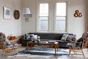 cow hide rug rectangular wooden coffee table modern sofa beige walls framed windows hanging lamp marble floor