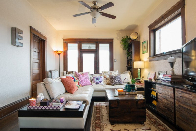 dark wood coffee table dark wood console table white sofa with multicolor accent pillows traditional area rug ceiling fan