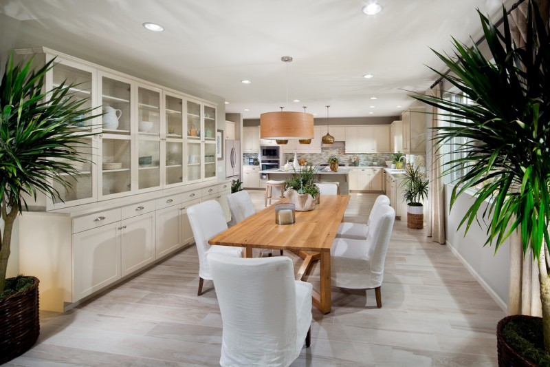 dining cabinet long row of cabinets table chairs wood floor plants lighting hanging lamps mediterranean style room