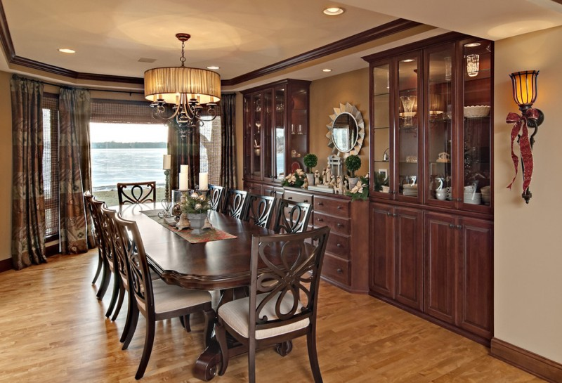 dining cabinet table chairs big windows curtains wall lamp wooden cabinets ceiling lights traditional room drawers mirror hanging light