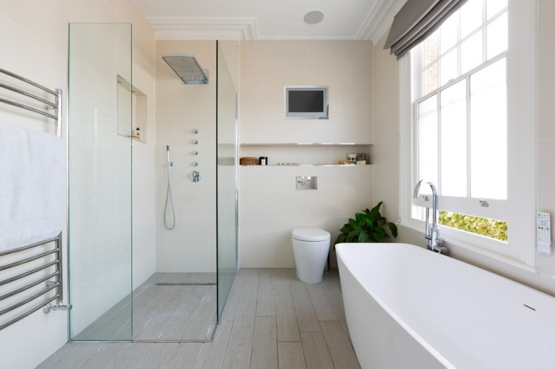 door less walk in shower glass divider white tub silver tap cream tiles bathrom wall wooden deck floor glass framed window