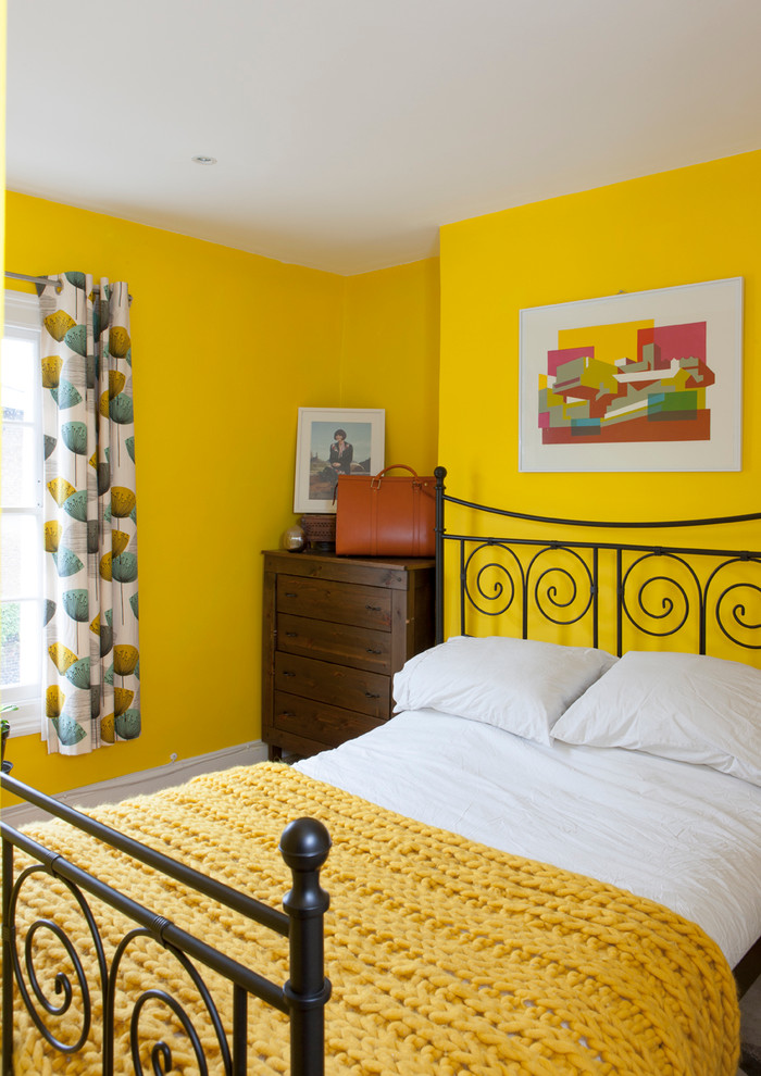 eclectic guest room with dazzling yellow painting walls dark wood console table black wrought iron bed frame with headboard hand knitted blanket in yellow
