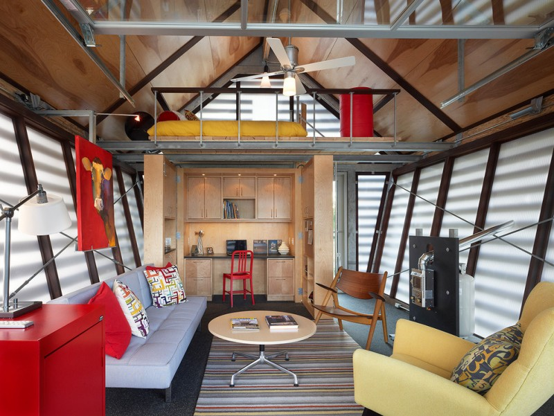 ecletic room in tiny house with yellw bed in battic bedroom with metal rail, red cabinet, grey cofa, stripped rug, metal beams, cream couch, wooden chair, wooden shelves
