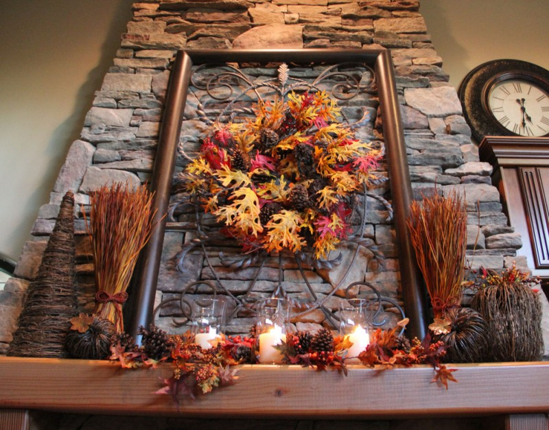 fall branches and pine cones some glass candle holders iron work fall mantel decoration