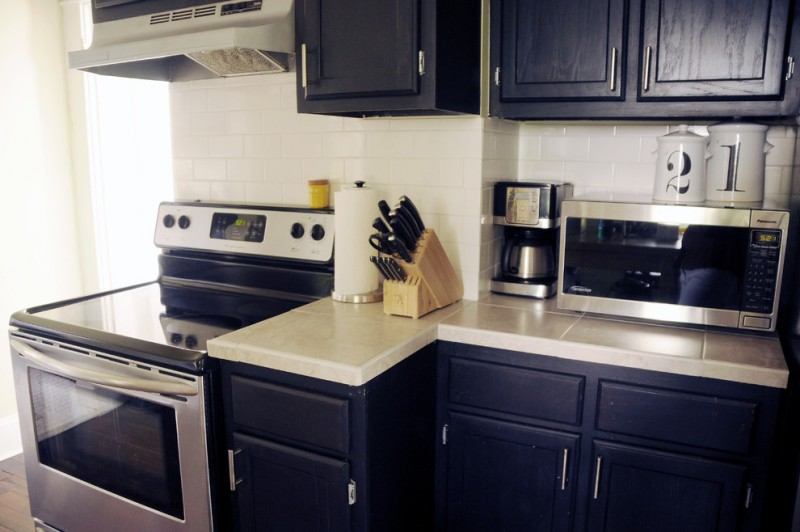 farmhouse kitchen navy blue cabinets white countertop stainless steel appliances