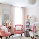 Girls Room With A Couple Of Pink Armchairs With Fluffy White Pillows Feathered Chandelier Silver Toned Center Table In Round Shape Fluffy White Area Rug White Shelving Unit Some Animal Stuffs