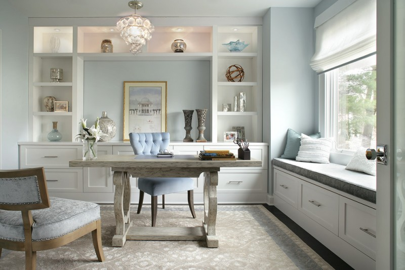 home office with white wall, white built in shelves and cabinet, chandelier, white tainted wooden table, blue chair, white rug, seating area beside the window with grey cushion