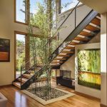 Indoor Planting Idea Wall Decor Staircase Stairs Pillows Wood Floor Small Stones Tall Plants Door Glass Ceiling Lamp