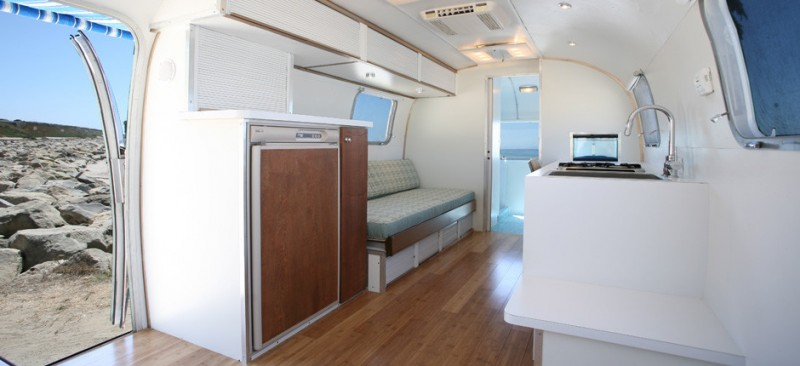 kitchen and living area in trailer with wooden flooring, white chair with white cushion