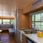 Kitchen In Trailer With Nude Top, Sink, Dining Corner Area, Dining Table