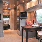 Kitchen In Trailer With With Wooden Cabinet, Sink, Plywoods Flooring, Wooden Table, Chair, Wooden Framed Refrigerator, Aluminium Storage